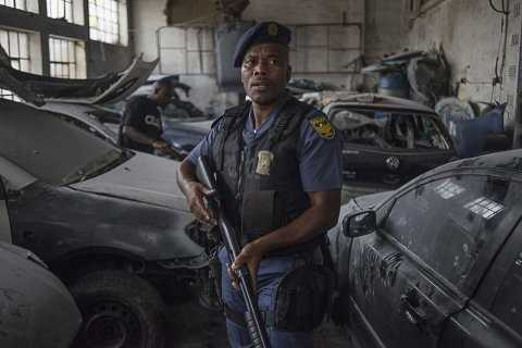 A police officer protects the property of foreign nationals in the Jeppestown area of Johannesburg(Mujahid Safodien:AFP)