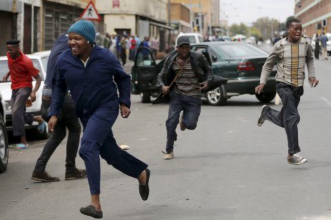 Locals run after trying to rob a foreign motorist in Johannesburg(Siphiwe Sibeko:Reuters)