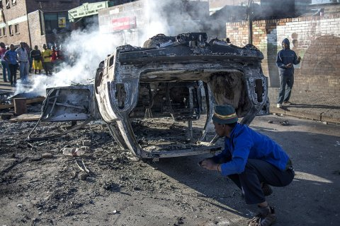 People look at a burnt-out car after foreign nationals reportedly torched it in the early hours outside a hostel in the Jeppestown area, east of Johannesburg(Mujahid Safodien:AFP)