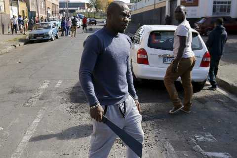 An African immigrant holds a machete in a run-down district of east Johannesburg(Siphiwe Sibeko/Reuters)