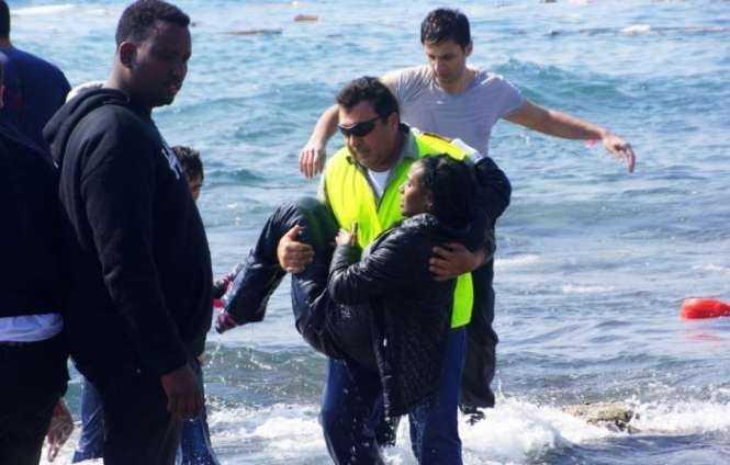 A man rescues a migrant from the Aegean sea on the island of Rhodes. Photograph- Argiris Mantikos:AP