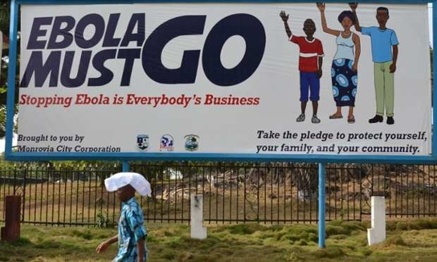 A man walks past an ebola campaign banner in Monrovia. Photograph: Zoom Dosso/AFP/Getty Images