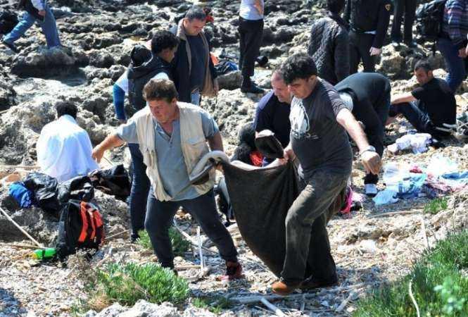 Men carry a body inside a blanket on the Rhodes seashore. Photograph- Nikolas Nanev:AP