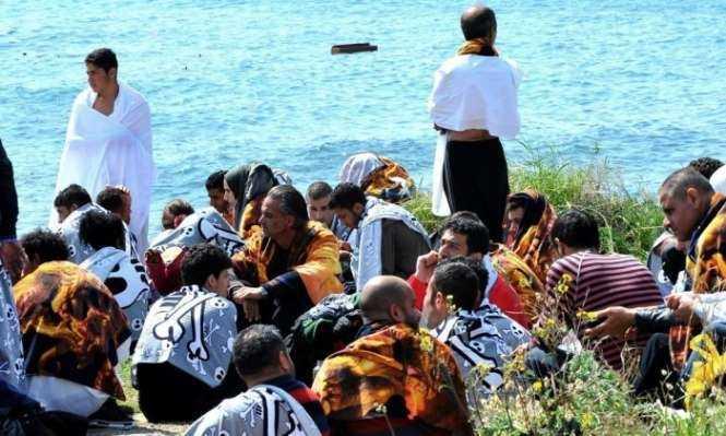Migrants recover from their ordeal on the Rhodes seashore. Photograph- Nikolas Nanev:AP