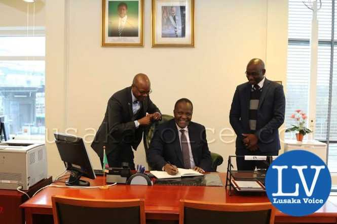 Finance Minister hon Felix Mutati smiles after signing the Visitors Book at the Embassy of Zambia in Stockholm, Sweden  n_a