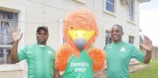 """Sports Minister Moses Mawere with FAZ President Andrew Kamanga posing with U20 AFCON Championship mascot """"Nkwazi"""" at Football House."""